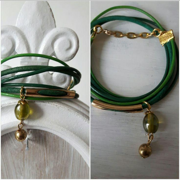 Wrap armband van smal groen leer met leerschuiver, een bedel van groen glas en goudkleurig metaal. De armband heeft een verlengketting.
