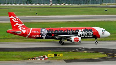 AirAsia (MY) Airbus A320-214 9M-AFA aircraft, painted in ''The Apprentice Asia'' special colours Mar. 2013, with the sticker '' AXN'' on the airframe,skating at Singapore Changi  International Airport. 26/08/2015. (The Apprentice Asia=an Asian reality game show from June-July 2013). (AXN=a pay cable & satelite TV channewl). (The plane has been withdrawn from use 22/07/2016).