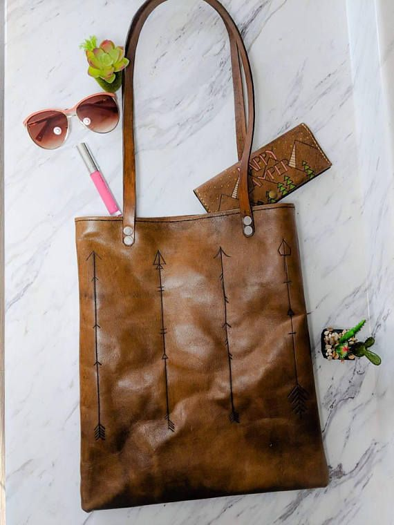This is a handmade customized genuine leather handbag. The bag itself is made from high quality vegetable tanned cowhide and the strap Is made from vegetable tanned cowhide. A unique arrow design is etched with unique arrows. This bag comes with or without a snap, please specify at