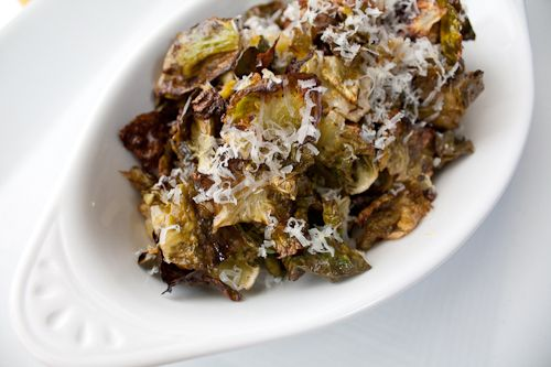 Roasted brussels sprout chips - 1 pound Brussels Sprouts, 3 tablespoons olive oil, ½ teaspoon salt, ½ teaspoon pepper, Juice of half a lemon, Zest of one lemon, ¼ cup grated Parmigiano Reggiano