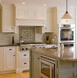 sage green and white kitchen color scheme with light sage green subway tiles and geometric design behind cooktop. White kitchen cabinets along walls and sage green island cabinets with built-in microwave and granite countertop - like the vent