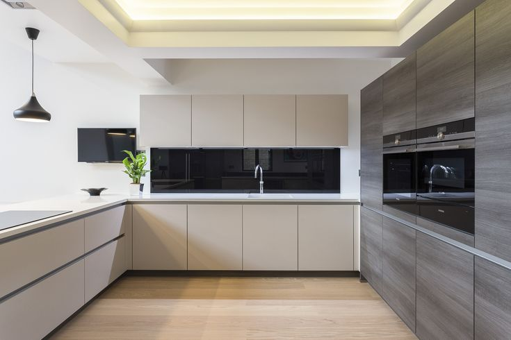 Modern Handleless Nolte kitchen in Feel and Manhatten ranges. This ultra-modern and sleek kitchen is complemented with black glass splash backs and a breakfast bar.
