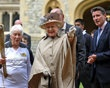 This image made available by LOCOG shows Queen Elizabeth II, center, and the Duke of Edinburgh, obscured, greeting Torchbearer 073 Gina Macgregor, left, and Olympic chairman Sebastian Coe right, outside Windsor Castle, Windsor, England Tuesday July 10, 2012. (AP Photo/Chris Radburn/LOCOG)