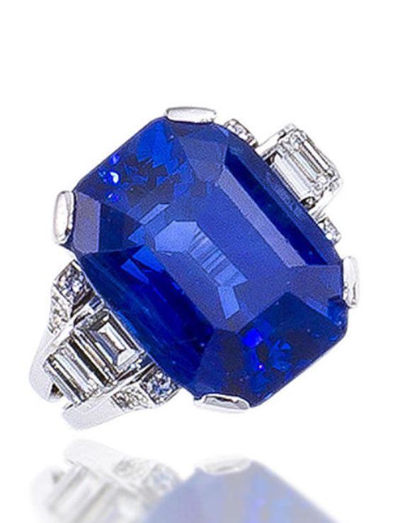 A sapphire and diamond ring centering a cut-cornered rectangular-cut sapphire, weighing 24.16 carats, with baguette and single-cut diamond scrolling shoulders and a bifurcated mount; mounted in fourteen karat white gold