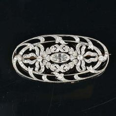 A belle époque diamond brooch, circa 1905, in the Garland Style, the oval openwork plaque set at the centre with a marquise-shaped diamond within a wreath and ribbon bow border, millegrain-set throughout with old brilliant and single-cut diamonds