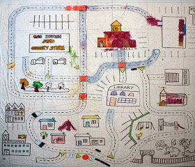 Tape a plain shower curtain liner to the floor, and draw roads and a community with a Sharpie. Kids can color it how they want, and when they're finished, can keep it to drive their cars on.