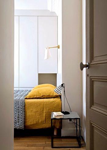 こちらのポイントはマスタードカラーのベッドリネン。大きな家具に色味を使ったら、その他をとことんシンプルにまとめるのがパリのアパルトマン風。