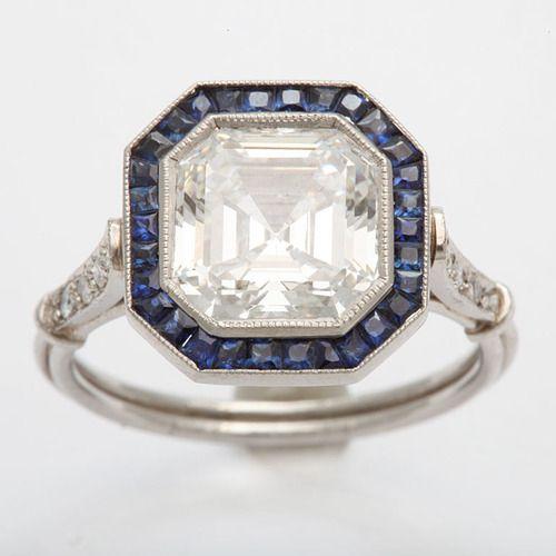 Art Deco Emerald/Asscher cut diamond engagement ring France 1930's. A stunning Emerald/Asscher cut 3.13 ct VS 1 F diamond is surrounded by sapphires.