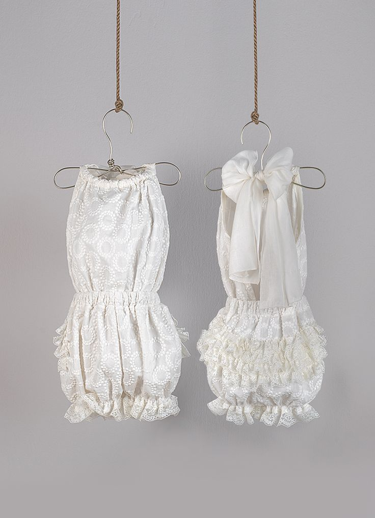 Ecru backless overall from embroidered cotton fabric. Ties at the neck with a scarf of cotton silk fabric and has decorative lace gathered on the back    Ecru  straw hat decorated with handmade flower made in embroidered voile and organza striped bow