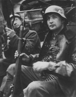 Czech insurgents wearing German uniforms and armed with Karabiner 98k rifles near a street barricade in Czechoslovakia during the Prague uprising.