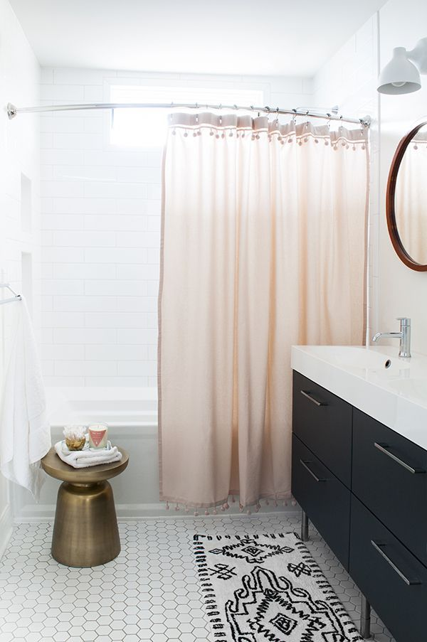 patterned tile in the bathroom with dark elements and a light pink shower curtain