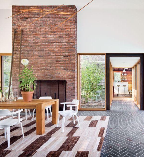 modern rustic dining room with brick fireplace and herringbone floors | via coco+kelley