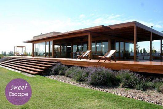 Em meio ao campo, o vidro foi utilizado em todo o entorno casa e a madeira serviu com estrutura das paredes e para o grande deck que ficam em torno da casa, criando assim uma deliciosa varanda com sofá e espreguiçadeiras