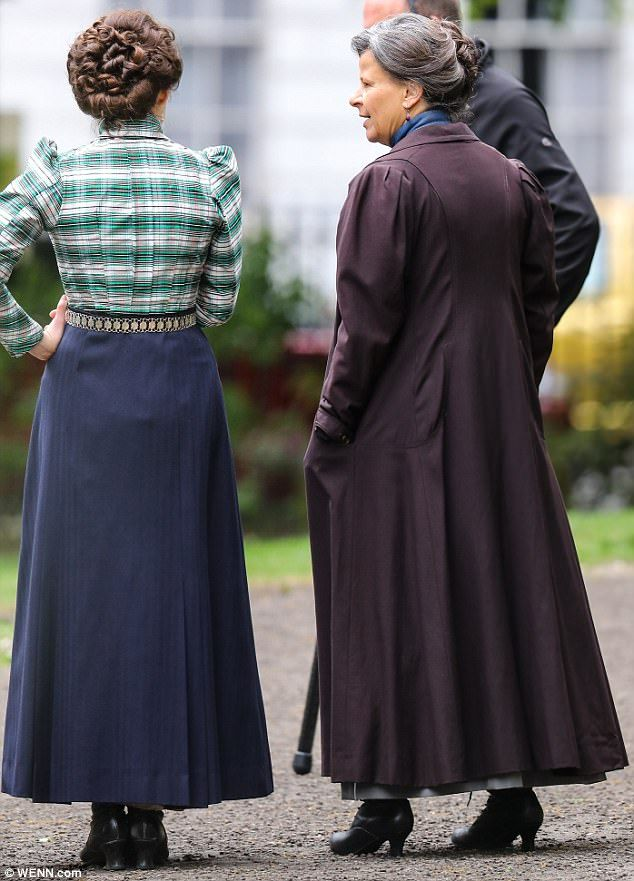 Turn of the century fashion: Both women wore ankle grazing boots and conservative puffball shirts as they filmed outside in a London park