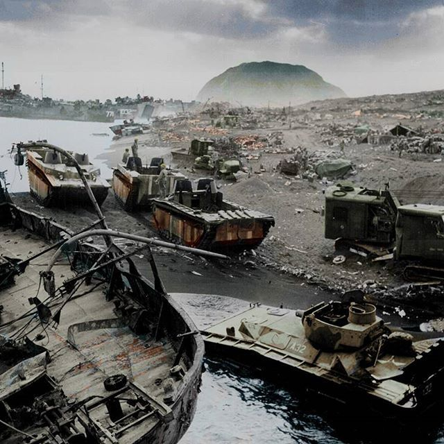 the_ww2_memoirs The ghastly and rusting remains of vehicles and LVTs litter the beaches of Iwo Jima with Mount Suribachi poking out of the smoke and fog, February, 1945. This photograph is so powerful and provoking it's indescribable. The rusting and deca
