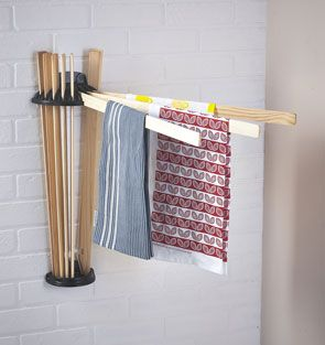 The radial clothes airer attached to the wall within the laundry. Two wooden airing laths are extended whilst the rest remain closed.
