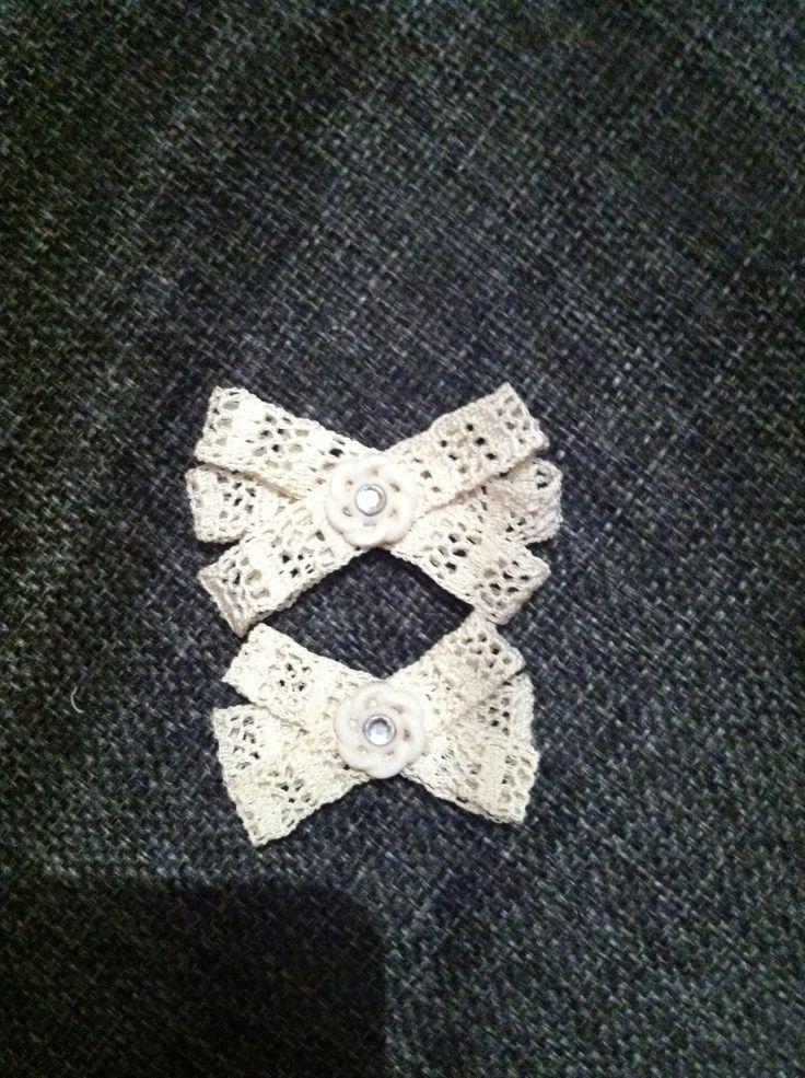 Två små rosetter av spets, dekorerade med knapp och strass.