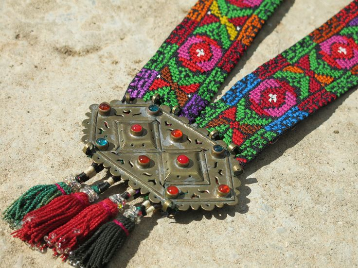 ETHNIC TREE: Ethnic necklace whose base comes from a vintage Palestinian cross-stitched belt. The bronze centerpiece is Turkoman and comes from Afghanistan. The tassels are vintage Uzbek. They come from old tapestry. This necklace is entirely handmade and is a unique piece. www.ethnictree.com