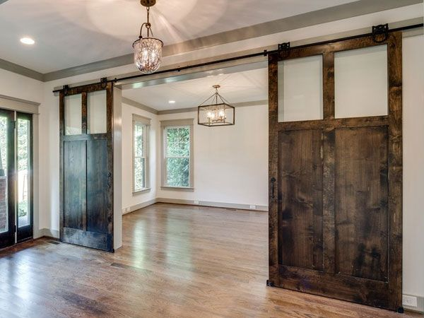 In this open-concept home, large sliding barn doors are used to create a little privacy as needed, without permanently closing off the rooms. High windows on the door design allow for light to pass between the rooms.