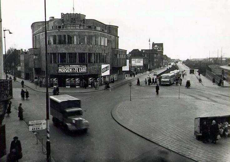 """Het stationsplein in 1950, de affiche van de film """"Morgen is te laat"""" verraad dat deze opname in Oktober1950 gemaakt moet zijn. Links de Stationsstraat, rechts naast de Roijal bioscoop de Parallelweg met daar zichtbaar een muur reclame van de Peugeot garage Nefkens. Op de achtergrond gezellenhuis Ons Thuis.Rechts in de helling staat de bus naar Hoensbroek van de fa Mulder. Door ons kwajongens meestal de """"Buldermus"""" genoemd, dit ipv de Mulderbus :-)"""