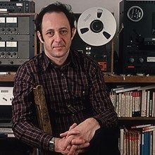 Portrait of American composer Steve Reich posing in front of recording equipment and reel-to-reel ta