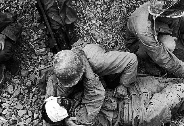 A soldier from the US 7th Army Division comforts a wounded comrade during the fight for Okinawa, Japan, May 1945.