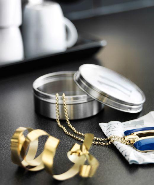 Detail nádoby z nehrdzavejúcej ocele s otvoreným vrchnákom a šperkmi položenými vedľa.