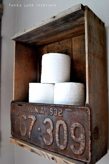 The toilet paper crate... Simplicity at its finest... old box with rusty old license plate, perfect wall storage.