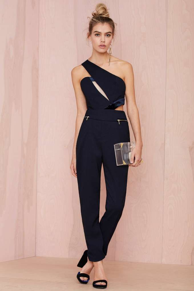 This tailored midnight blue jumpsuit by Three Floor has a one-shoulder neckline with mesh and cutout inserts, velvet detailing, and gold zip closures at front pockets and side.