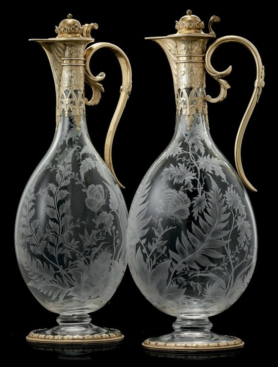 A PAIR OF VICTORIAN SILVER-GILT MOUNTED GLASS CLARET JUGS  MARK OF G. FOX FOR C.T. & G. FOX, LONDON, 1866  Oval, engraved in the style of Joseph Keller with butterflies and ferns, the siver-gilt foot and neck mounts, scroll handles and hinged covers with foliage, marked on feet, necks and covers 12½ in. (31.8 cm.) high (2)
