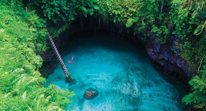 """TO SUA OCEAN TRENCH – SAMOA  A tradução para To Sua é o """"grande buraco"""". Para ter acesso a essa fantástica piscina natural de águas cristalinas é preciso desder uma escada de cerca de 30 metros de altura. Cercada por uma vegetação maravilhosa na ilha de Upolu é um dos lugares mais incríveis pra dar um mergulho."""