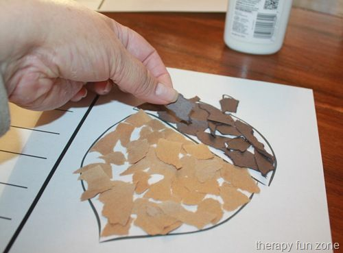 The individual must place colored paper pieces into the correct section in order to create the image of an acorn.