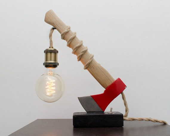 Desk Lamp - Table Lamp - Steampunk Desk Lamp - Industrial Desk Lamp - Steampunk Table Lamp - Bedside Light - pipe lamp - Ruga   The rustic design of Ruga is created with a classic Red Axe inserted into a wooden base.  Rope cord is passed through the axe and twisted around its handle which drops to a large bronze colour socket.  The G80 bulb fits well with Ruga.  Simple on/off toggle switch.  It has a thick rectangle wooden base hand painted with a waterproof ebony paint.  The axe's sharp...