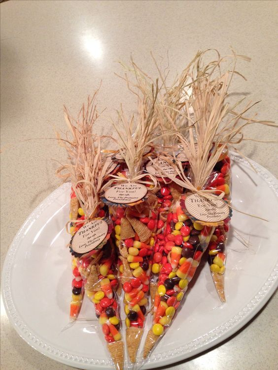 Thanksgiving place setting or thank you gift. Easy to make. I filled icing bags with a mix of Reeses pieces, candy corn, and bugles. Add rafia  to the top and tie with a bow.: