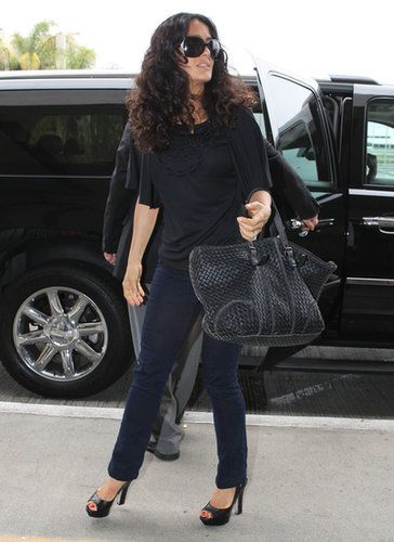 Salma Hayek went for all-black everything in her draped top, which she styled with sleek jeans, a pair of peep-toe pumps, and the ultimate carry-on: a Bottega Veneta bag.                   Source: FameFlynet