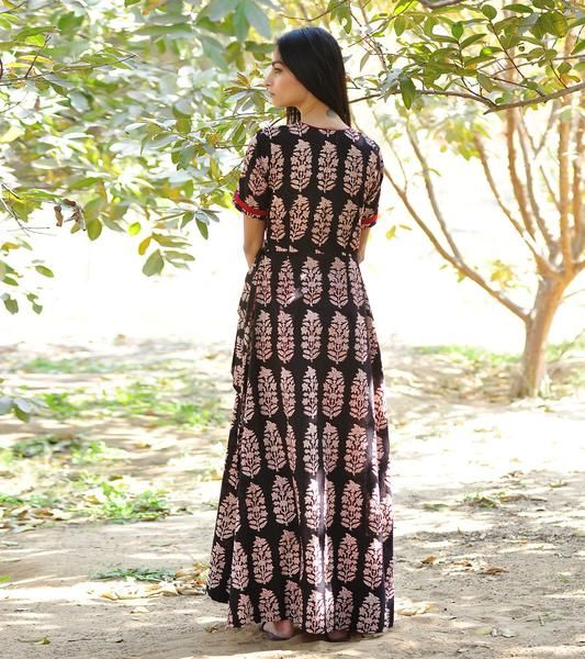 Make an entrance in this ethereally draped black block printed cotton gown. The design features short sleeves, side pockets, an beautiful flare, that is fasten