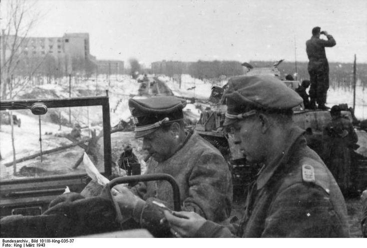 Fritz Witt SS-Sturmbannführer, Waffen SS (left) in staff car examines map, Russia, March 1943.