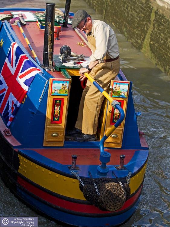 Flat cap & narrow boat in canal lock