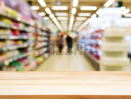 Wooden board empty table in front of blurred background. Perspective light wood over blur in supermarket - can be used for display or montage your products. Mock up for display of product.