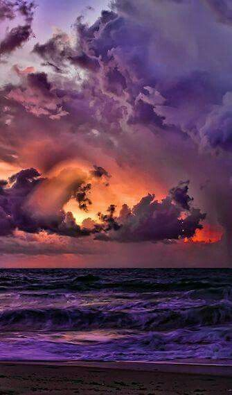 At the end of the day a kaleidoscope of colors swirl above a reflective ocean.