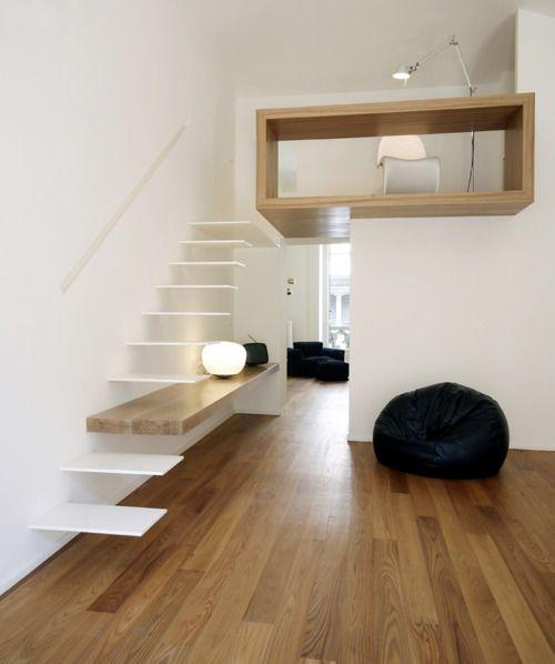 Loft com uma discreta e moderna escada/ escrivaninha.