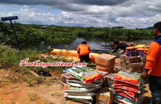 Petugas BLHPBD mendistribusikan bantuan makanan untuk korban banjir di Dusun Telayar Desa Sejegi Kec. Mempawah Timur./ leo AR