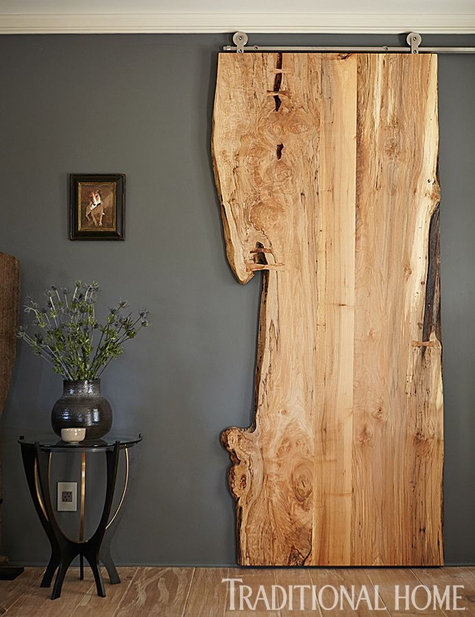 If it weren't for that metal track this piece of live edge wood would never suggest it actually serves as a door. Love! Just slightly paler...