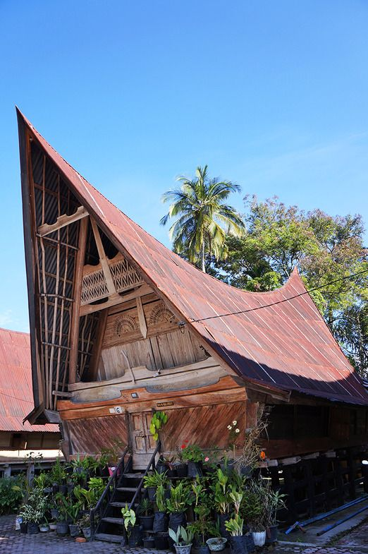 Indonesia--Batak Toba house is boat-shaped with beautifully carved gables and sweeping ridges. The pillars at the bottom section symbolize the bottom of the earth, while the house's main building represents the world and the roof, built to soar high, symbolizes the sky. Photo by Keshie Hernitaningtyas.