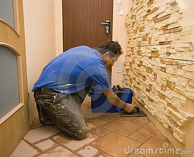 A man working at a new floor tiles, cleaning them with water.  <a href='http://www.dreamstime.com/interiors-rcollection5192-resi208938' STYLE='font-size:13px; text-decoration: blink; color:#FF0000'><b>HOME BUILDING & RENOVATION »</b></a>