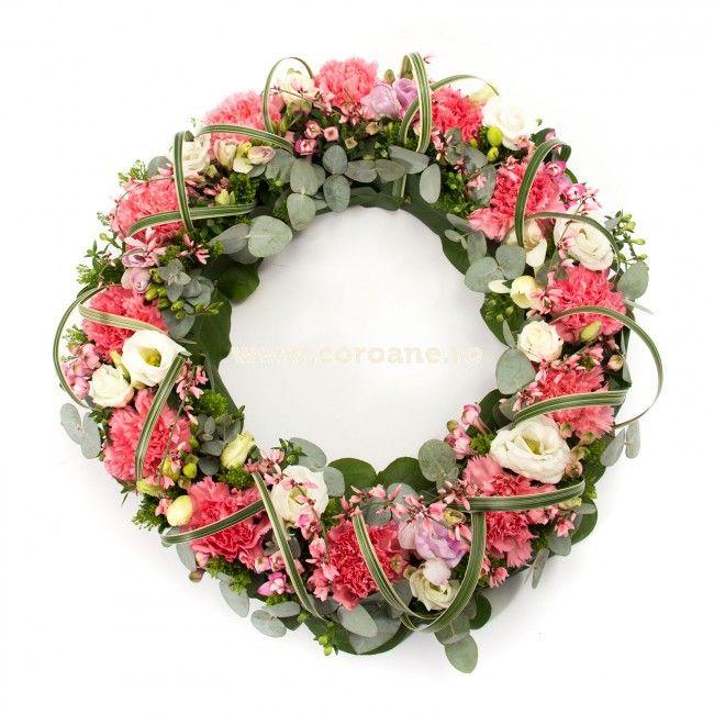 Coroana eleganta mini, un ultim omagiu discret, simplu si delicat. Coroana are un diametru de 50 cm si este realizata pe burete floral umed. Aranjamentul coroana funerara este creat din garoafe, lisianthus si ginster, alaturi de verdeata speciala.