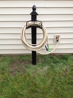 Build your own garden hose reel. 4 foot treated post, treated 1x6 cut to 5x5 and 4x4 with a fence post finial. Buy a wall mount hose reel (Lowes had pretty ones). Mount real onto post. Spray all with outdoor spray paint color of choice. Dig post hole 2' deep. Anchor with quikrete. Stand back and admire your work.