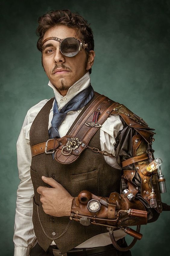 Monocled Steampunk Man - Large glass monocle, high collared shirt, tie, waistcoat (vest), pocket watch, trousers, steam-powered bracer/mechanical arm. Men's Steampunk fashion inspiration! - For costume tutorials, clothing guide, fashion inspiration photo gallery, calendar of Steampunk events, & more, visit SteampunkFashionGuide.com