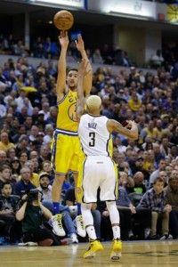 Klay Thompson, de los Warriors de Golden State, se eleva sobre la defensa de George Hill, de los Pacers de Indiana, para anotar un canasto en acción del partido de ayer en el baloncesto de la NBA.