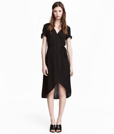 Musta. V-aukkoinen mekko kreppikangasta. Lyhyiden hihojen suissa solmusomisteet. Kietaisumallinen etukappale, jossa vyötärölle solmittava nauha.